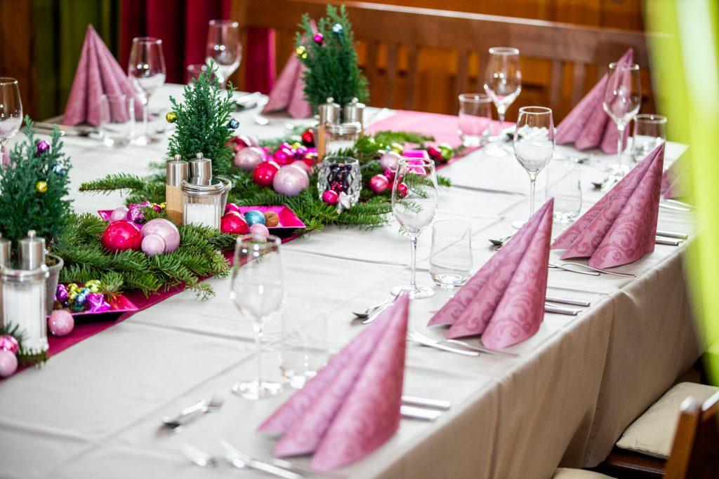 Festlich gedeckter Tisch für Weihnachten mit bunten Kugel und Tannenzweigen