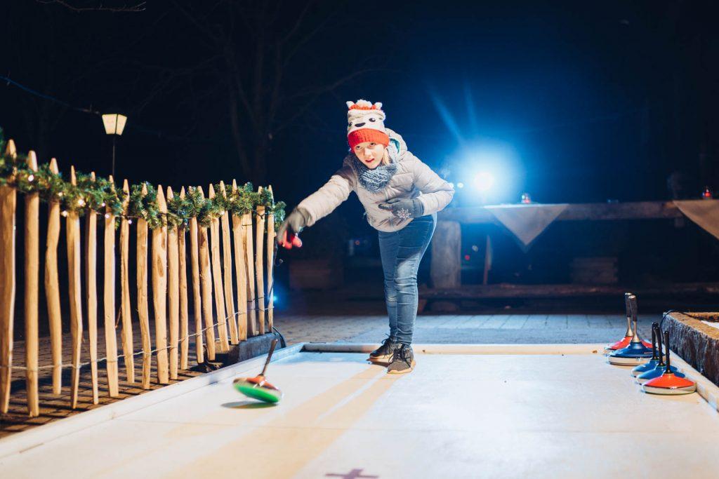 Eisstockschießen bei Nacht auf der Beleuchteten Kunsteisbahn im Biergarten der Landlust